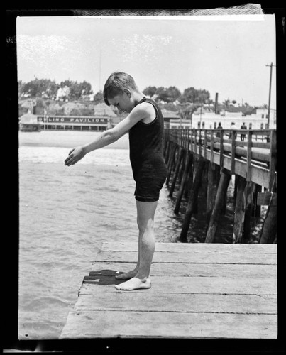 Boy in diving pose at end of North Beach Bath House Pier, Santa Monica