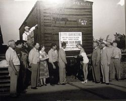 "Ribbon cutting ceremony in front of a railroad car, ""First Car No. 1,"" carrying Gravenstein apples from Sebastopol and the Sebastopol Apple Growers Union, about 1940s or 1950s"