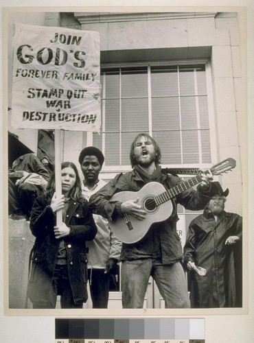 There were a large number of Christian anti- war slogans on picket signs - singer was singing about finding true peace with Jesus. U.C. rally moratorium, steps of Sproul Hall, University of California, at Berkeley