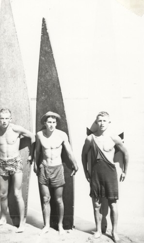 Rich Thompson, Harry Mayo, Bob Gillies in front of surfboards at Cowell Beach
