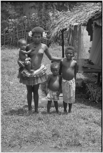 Adolescent girl wearing short fiber skirt and necklace, holds infant, younger children stand nearby