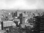 [Cityscape from above circa Kearny and Post Sts. looking northeast toward Wholesale District. Telegraph Hill in distance, left; Merchants' Exchange Building and Mills Building, center]