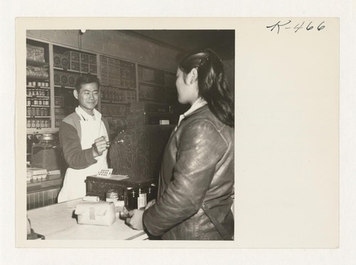 Shig Nishimoto rings up a sale in his newly opened general merchandise store. Shig had worked for one year in Benton Harbor, Michigan, after spending two years at Minidoka Relocation Center. He also owns several orchards around Penryn. Photographer: Parker, Tom Penryn, California
