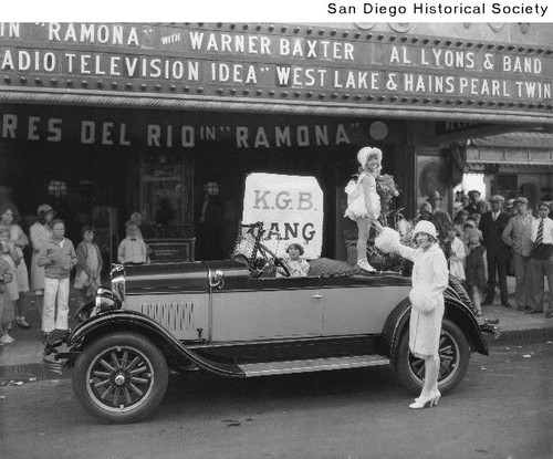 A young girl standing on the back of a 1928 Durant automobile parked in front of a movie theater