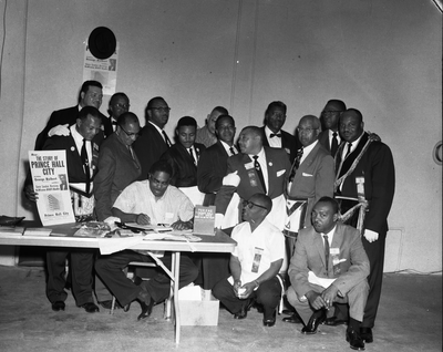 "George Holbert at book signing table, man holding up placard ""The Story of Prince Hall City"""