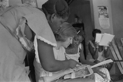 Nina S. de Friedemann and a woman looking at pictures, San Basilio del Palenque, ca. 1978