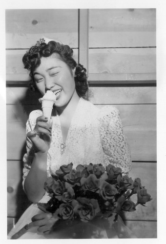 Labor day queen eats an ice cream cone and winks at the photographer at the celebration which was held after the coronation ceremony and was only part of the celebration at this relocation center. Photographer: Stewart, Francis Newell, California