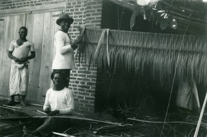 Men making roofs, in Oyem, Gabon
