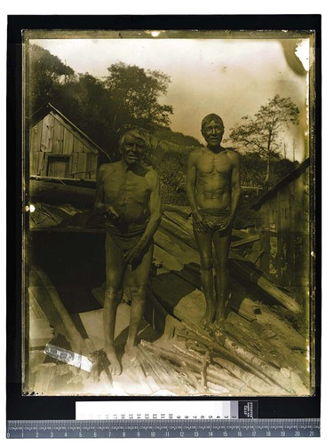 [Two men posing at entrance of a sweat house]