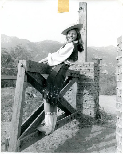 Publicity Photo of a cowgirl on a gate for the Malibu Remuda, 1947