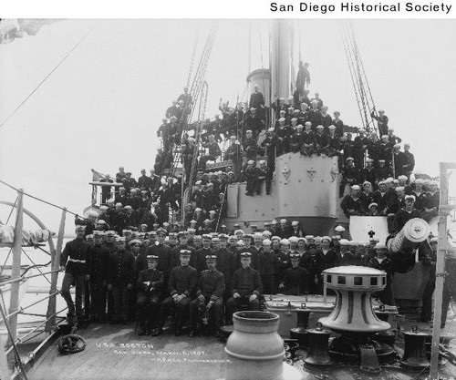 The officers and crew of the USS Boston posing on the deck in San Diego Harbor
