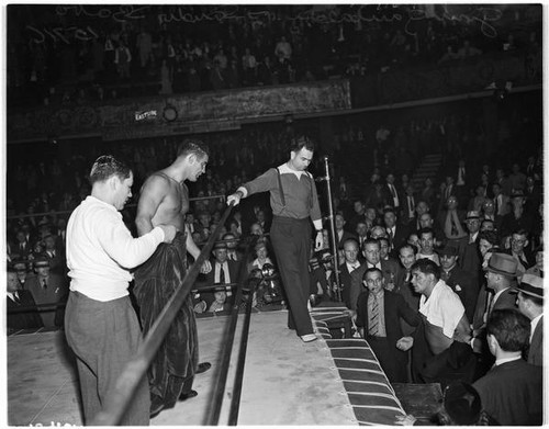 Heavyweight wrestler Gino Garibaldi looks down at opponent Sandor Szabo from the ring in Olympic Auditorium, Los Angeles, October 13, 1937