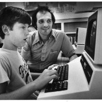 Jim Gallegos watches student Doug Wolfe learn computer at Merryhill School
