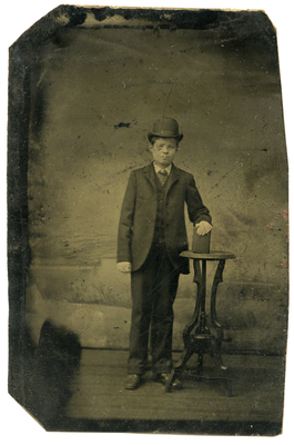 Tintype of a boy standing wearing a dark colored suit and a dark colored derby hat