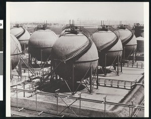 Exterior view of an unidentified oil refinery, showing rows of spherical tanks, ca.1940