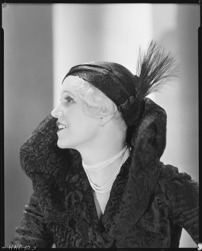 Peggy Hamilton modeling a Hortense hat and a coat with a high collar and flared cuffs, 1931