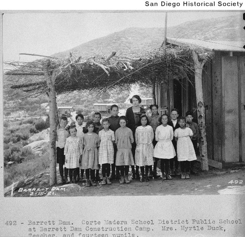 School children and their teacher standing at the entrance to their classroom at the Barrett Dam construction camp