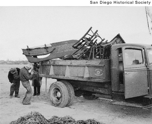 Men loading a City of Coronado truck with wreckage from the gambling ship Monte Carlo