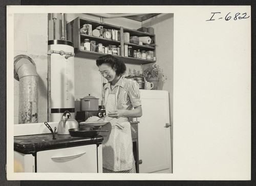 Mrs. Thomas Taneichi Kamikawa is preparing supper in the kitchen of the 4-room family unit which she occupies with her