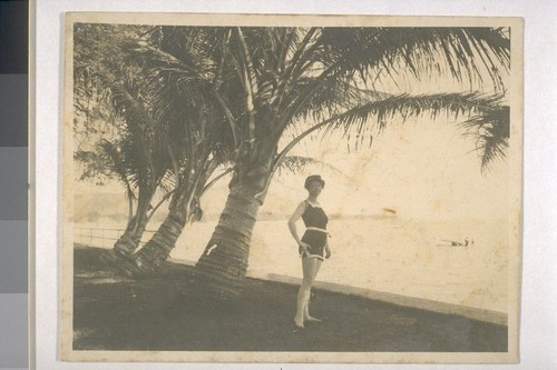 [Charmian London by palm tree on beach.]
