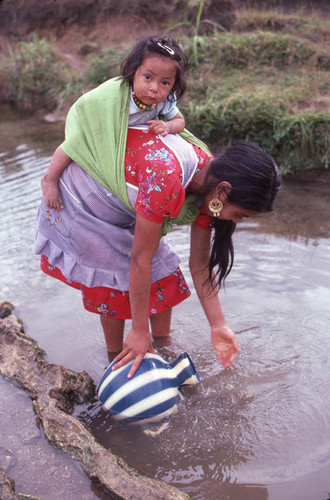 Guatemalan refugee collects water at a river, Cuauhtémoc, 1983