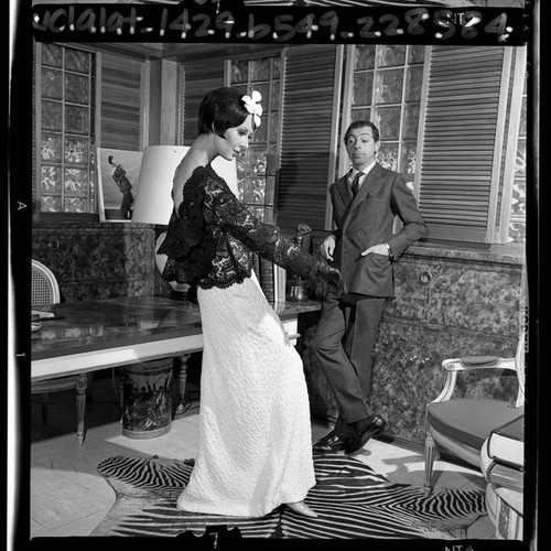 Fashion designer James Galanos with model wearing in one of his gowns, Los Angeles, Calif., 1965