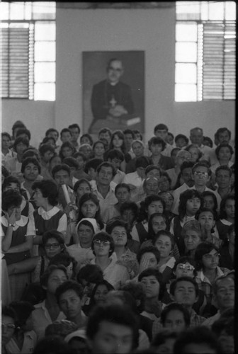 Crowd beneath a portrait of Archbishop Óscar Arnulfo Romero during a mass in his honor, San Salvador, 1983