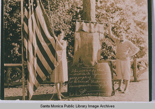 David Stratford and an unidentified woman raising the flag at the Institute Camp in Temescal Canyon, Calif