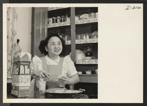 Mrs. Harvey Suzuki, who relocated with her husband from the Colorado River Relocation Center, is preparing a snack for him