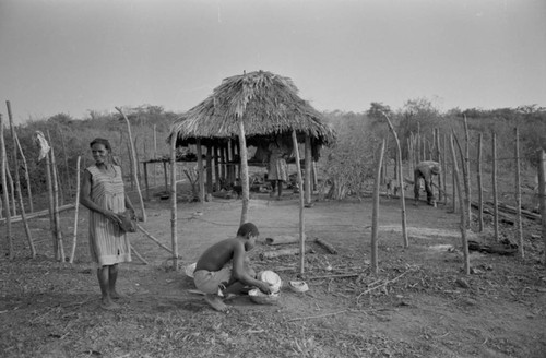Villagers working near a palapa, San Basilio de Palenque, Colombia, 1977