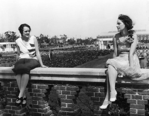 Two women sitting on wall