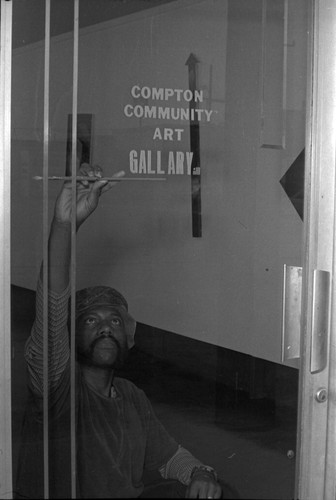 Image / Painter checking the name painted on a glass door & Calisphere: Painter checking the name painted on a glass door