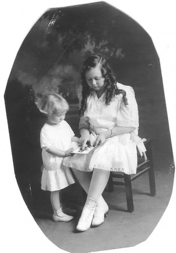 Bunni Cornelia E. Myers seated on a chair with a book and a younger child standing and looking at the book, circa 1915