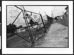 Young man of Hispanic origin jumping over the fence of a vacant lot, downtown, San Salvador