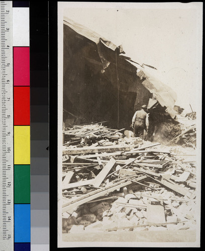 [Man walking in rubble, unidentified location.]