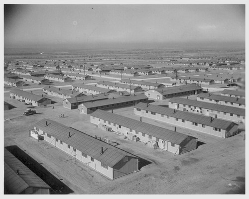 Overlooking the Amache Relocation Center, near Granada, Colorado. In the foreground is a typical barracks unit consisting of 12 six room apartment barracks buildings, a recreation hall, laundry and bathrooms, and the mess hall. Photographer: Parker, Tom Amache, Colorado