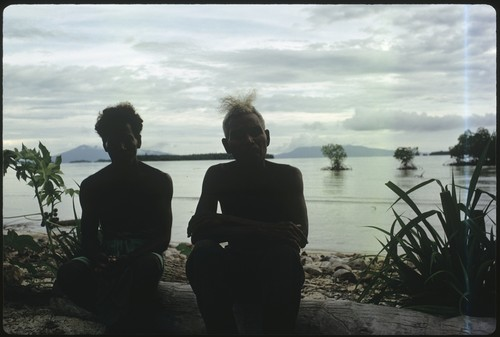 Two men seated at the shoreline