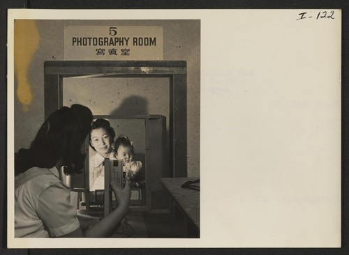 Yuki Shirakawa, Relocation Department Photographer, is taking a picture of little Dinne Oki for the file and identification card, as