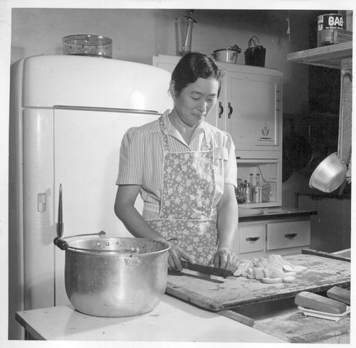 Mrs. Harumi Yamasaki is preparing dinner for her employer. She and her husband relocated late this spring to the farm of Mr. Edward Barron at Seabrook, Maryland near Washington, D.C. Here he has about 40 [20?] acres of vegetables under cultivation and Mrs. Yamasaki cleans and cooks for the Barrons.--Photographer: Van Tassel, Gretchen--Seabrook, Maryland. 7/21/44