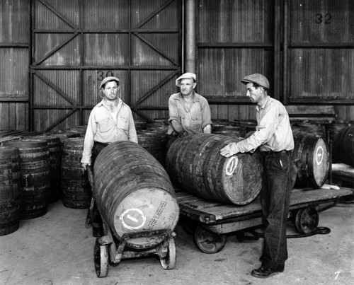 Men moving liquor barrels