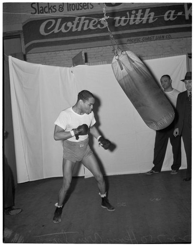Calisphere: Boxer Henry Armstrong trains with a punching bag, Los