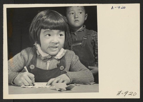 A third grade student at the Manzanar Relocation Center for evacuees of Japanese ancestry practices free hand drawing. This photo