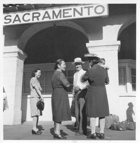Returnees from the Rohwer Relocation Center awaiting transportation to their homes in Sacramento. Roaring into Sacramento Monday morning, July 30