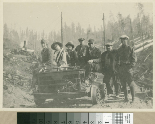 [4 men, 3 women posed on rail car in logged forest]