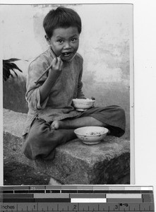 A young boy eating rice at Luoding, China, 1936