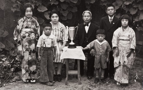 The Moriwaki Family of Oxnard: about 1934 ; back L-R: Masako, Masano (mother), Tokutaro (father), Norio ; Front: Noriyoshi, Takanori, Masami ; the trophy was presented to Mr. Moriwaki when he was President of Oxnard Buddhist Church