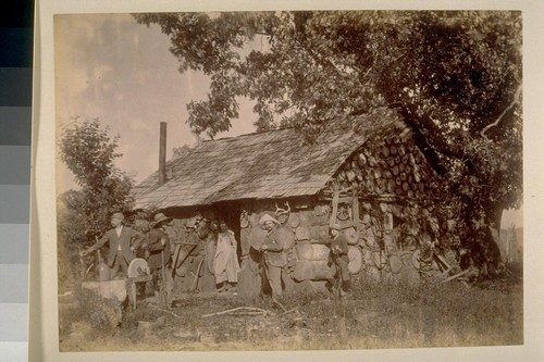 [Men with rifles and girl in doorway of log cabin]