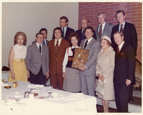 Governor Reagan holding the Art Piece--L to R: Front Row: Mrs. Brock, Clint Murchisson, Unknown, Nancy Reagan, Governor Reagan, Mrs. Seaver, Unknown; Back Row: Unknown, President Banowsky, Unknown, Chancellor Young, Dean Hudson, Vice Chancellor Runnels