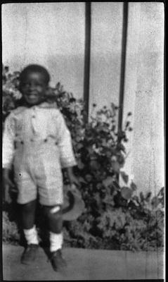 Young boy standing in front of house