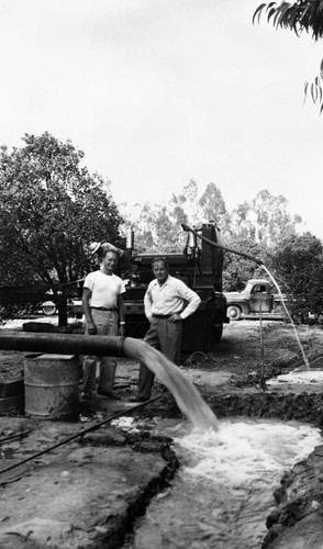 Tustin Water Works superintendent, Walter Rawlings, and Earl Rowenhorst watch water pour from a pipe as the La Veta well comes in, Tustin, ca. 1946